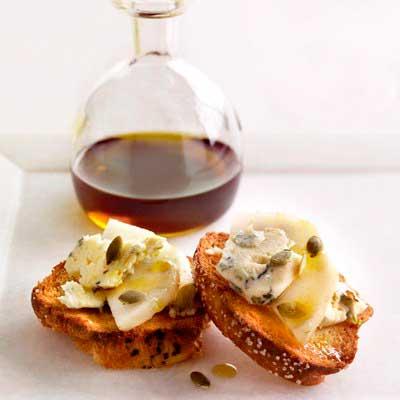 Кростини с сыром и грушами, сбрызнутые тыквенным маслом.